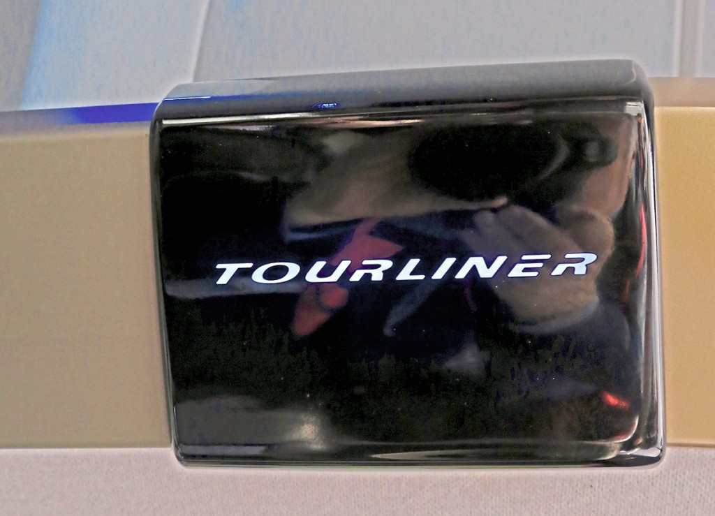 Illuminated Tourliner signs are featured at intervals along the luggage rack edges