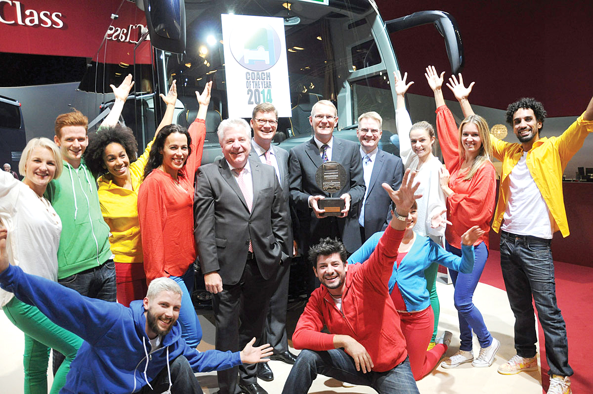 Hartmut Schick, CEO of Daimler Buses, collects the Coach of the Year 2014 trophy from Jury Chairman, Stuart Jones, surrounded by the Setra team and dancers.