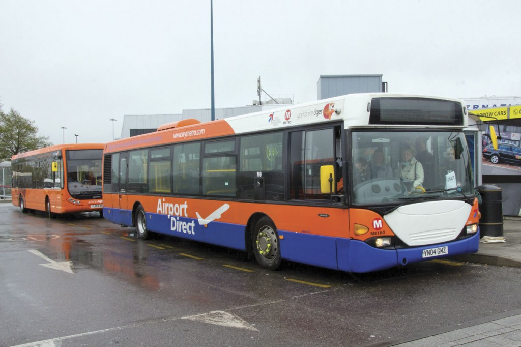 A Scania with the Airport Direct branding loads in the airport bus station for Bradford. The Leeds service behind is being worked by an Optare Tempo freshly refinished in Yorkshire Tiger's orange livery