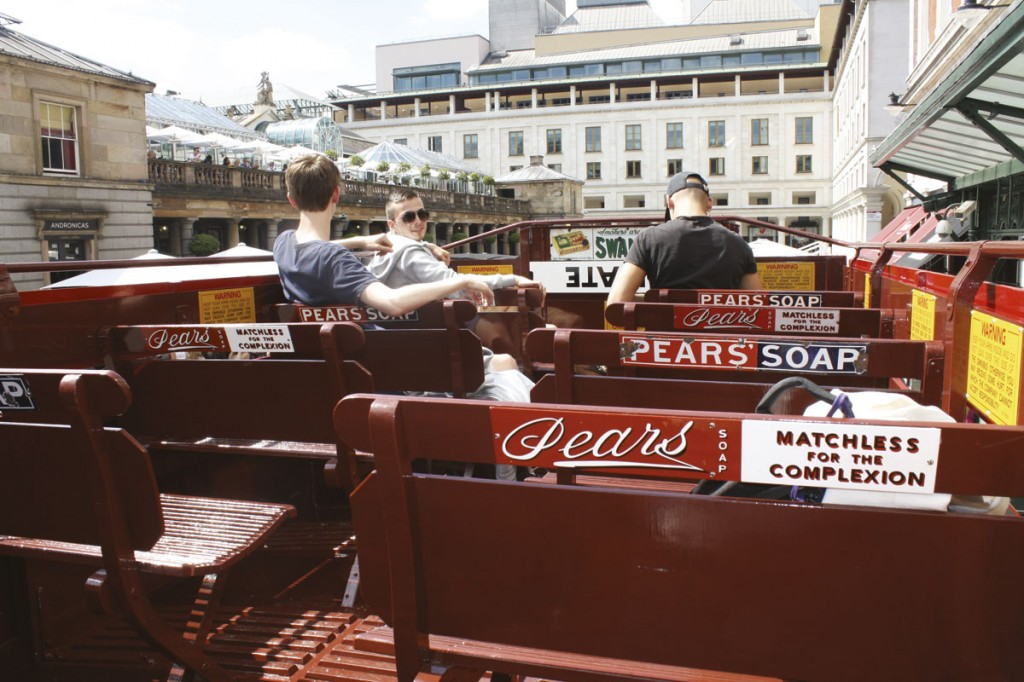 Visitors aboard the upper deck area showing the hard wooden seats, warning signs and advertising slogans of the day