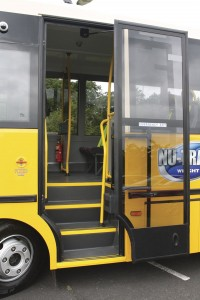 The entrance to the bus is beyond the front wheel due to the front engined truck chassis