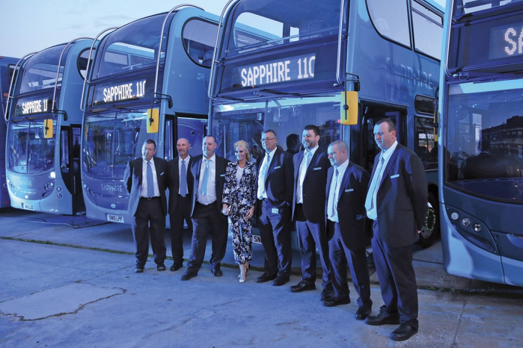 In the blue spotlights which bathed the site at dusk, drivers in Sapphire uniform pose for a picture with Chloe Sims