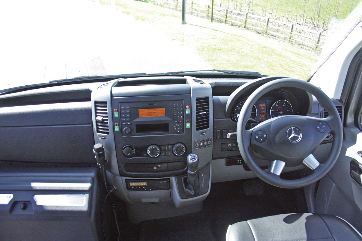 Note the function steering wheel and the neat body system controls grouped to the left of the driver.
