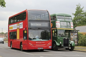 A Quality Line Enviro400 returning to depot passes a green RT duplicating on route 418