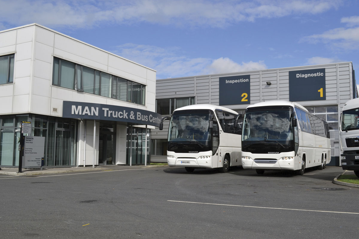 A Top Used twin axle and new tri-axle MAN Tourliner outside MAN Centre of Excellence at Manchester