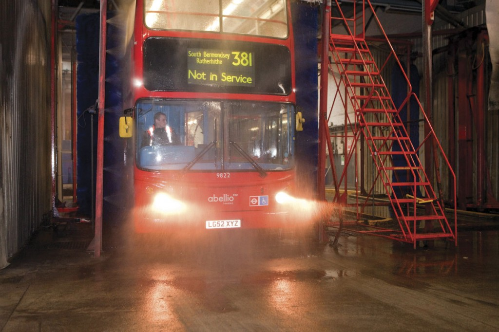 A Cordant employee taking one of Abellio's Tridents through the bus wash