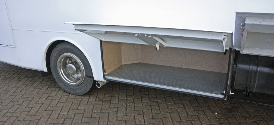 Underfloor luggage lockers are provided on both sides of the vehicle