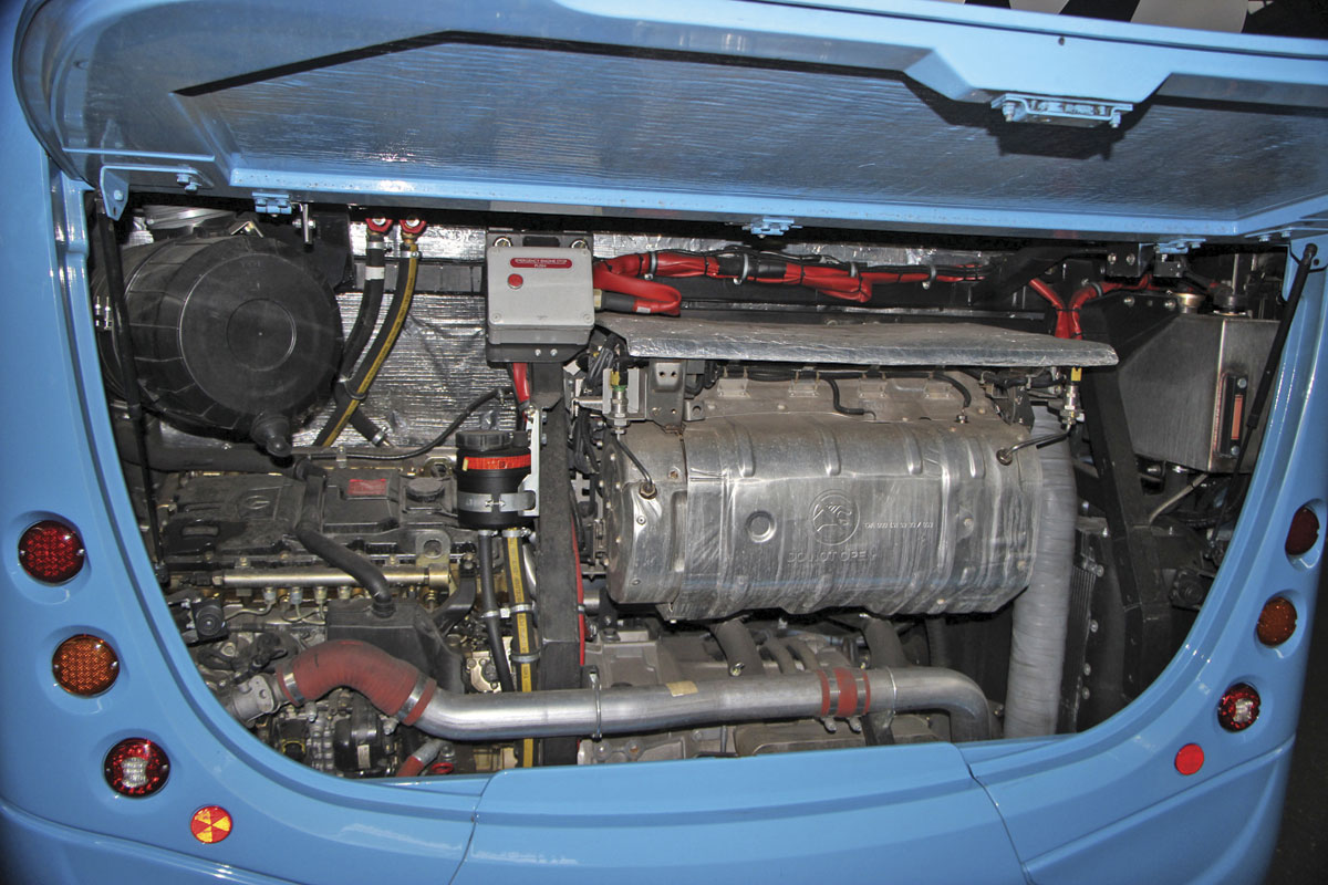 The engine bay with the exhaust system prominent. The hydraulic equipment associated with the steering will disappear when the system is electrified