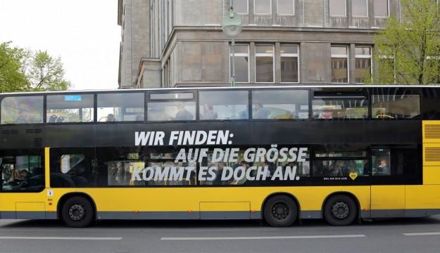 MAN double decker with 'Wir finden, auf die Groesse kommt es doch an' expression.
