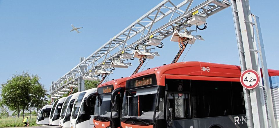A plane flies over the buses fast charging at Cateringweg depot. Buses from both fleets use these chargers