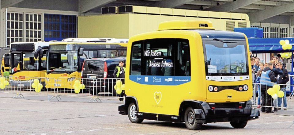 """The Easy Mile autonomous shuttle vehicle in action, the message on the side reads, """"we don't let anyone drive"""""""