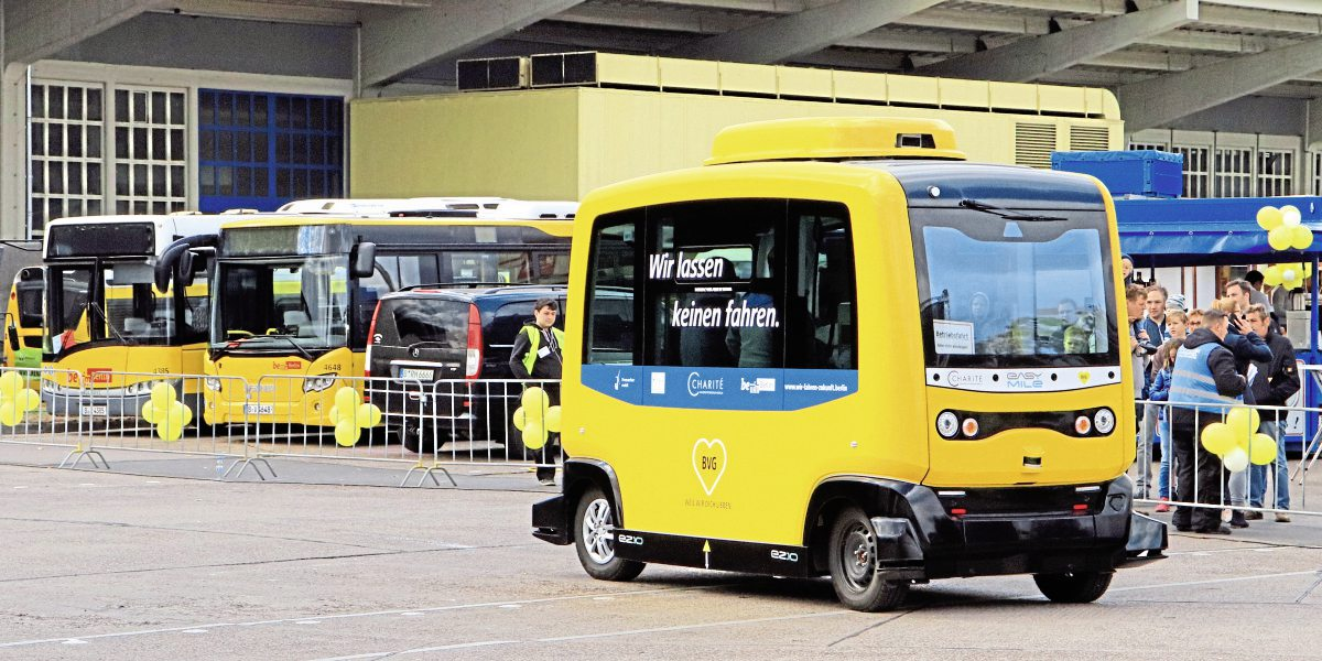 "The Easy Mile autonomous shuttle vehicle in action, the message on the side reads, ""we don't let anyone drive"""